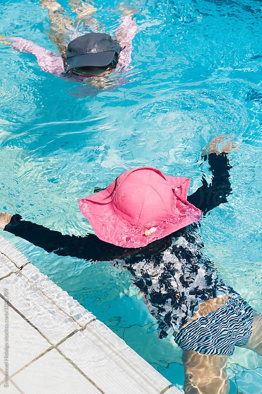 Tw friends swimming toward each other under water. by Emmanuel Hidalgo for Stocksy United