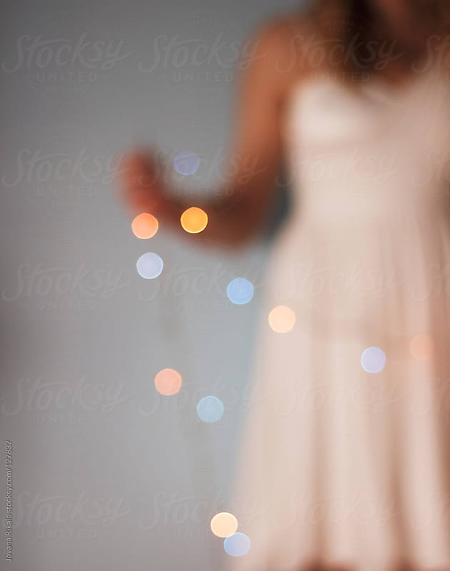 Girl holding Christmas lights in her hands,blurry by Jovana Rikalo for Stocksy United
