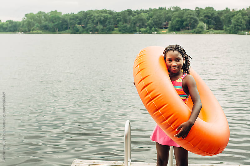 Smiling black girl holding an orange inner tube by Gabriel (Gabi) Bucataru for Stocksy United
