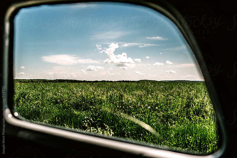 View of a field through a car window by Joseph West Photography for Stocksy United