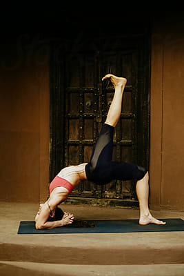 woman doing advanced pigeon yoga pose  stocksy united