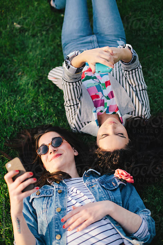 Two female friends having a good time outdoors by Marija Mandic for Stocksy United