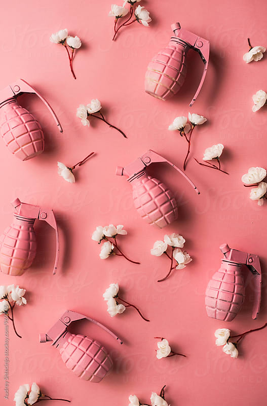 pink hand grenades with white flowers on pink background  by Audrey Shtecinjo for Stocksy United