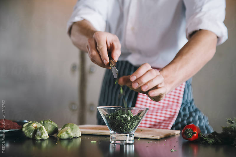 Cook putting chopped greenery in glass by Danil Nevsky for Stocksy United