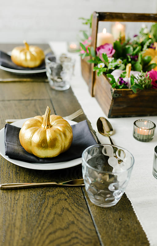 Golden squash on plate for Thanksgiving or Halloween table decor by Kirsty Begg for Stocksy United