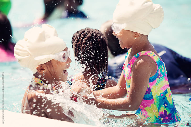 Portrait fo two sisters playing happily in a pool during summertime by anya brewley schultheiss for Stocksy United