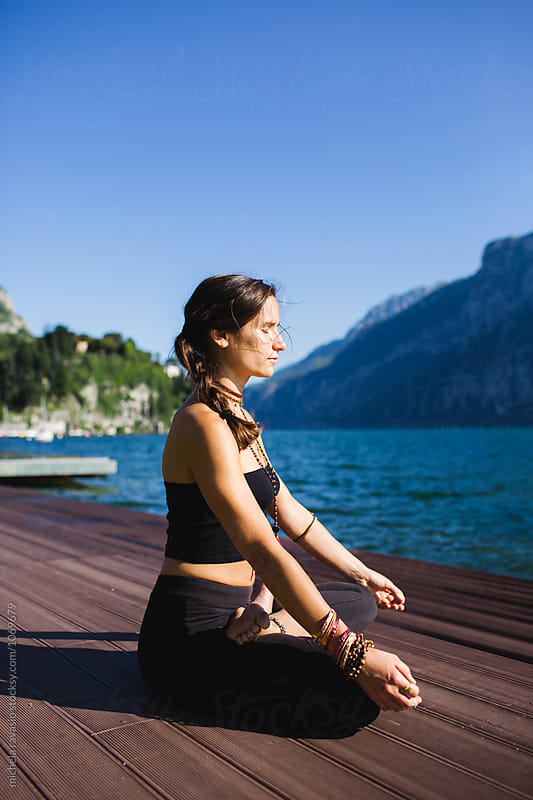 Brunette woman doing yoga pose by the lake by michela ravasio for Stocksy United