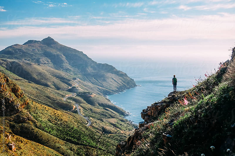 Hiker on overlooking a scenic mountain along the coast by Micky Wiswedel for Stocksy United