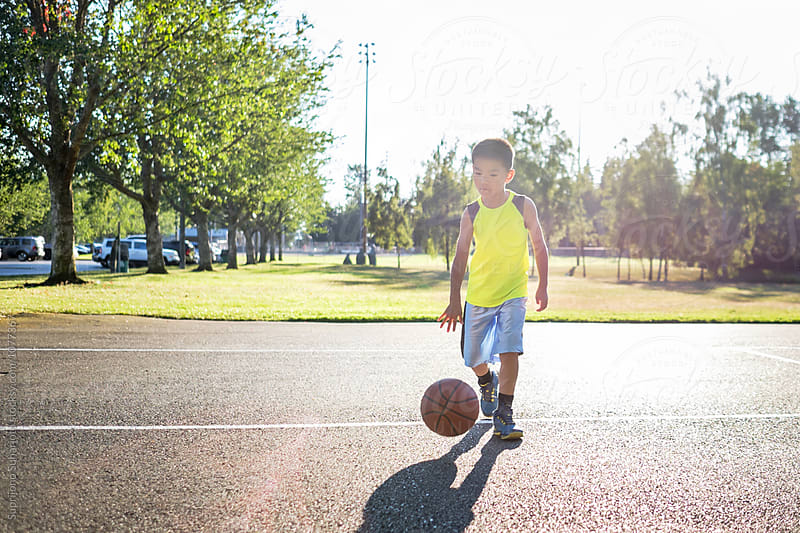 Asian kid dribbling a basketball in an outdoor basketball court by Suprijono Suharjoto for Stocksy United