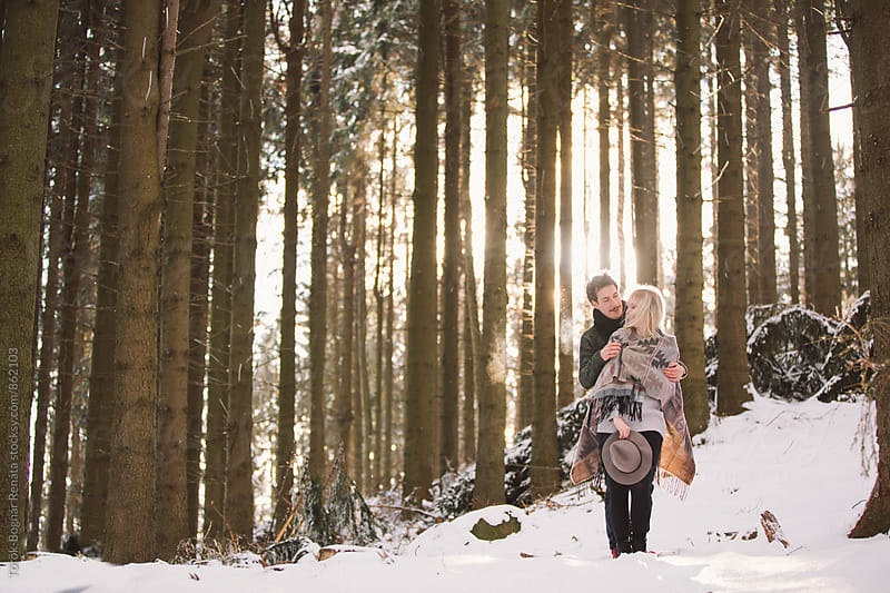 Lovely fashionable young couple in the snowy woods by Török-Bognár Renáta for Stocksy United