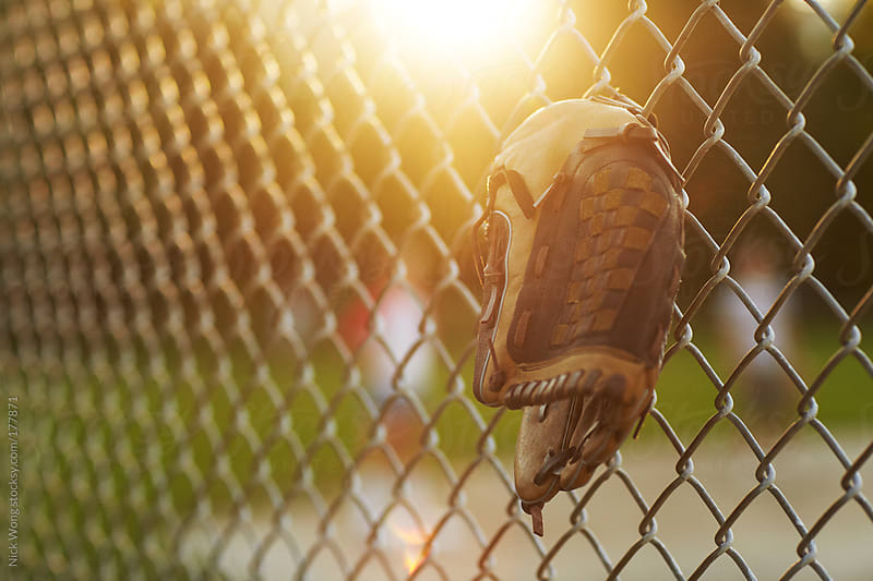 Baseball Glove hanging off Chain-link Fence during summer game. by Nick Wong for Stocksy United