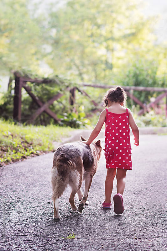 Little girl walking with her dog by Lea Csontos for Stocksy United