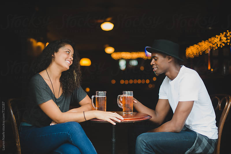 Young couple having a drink at the bar by Lauren Naefe for Stocksy United