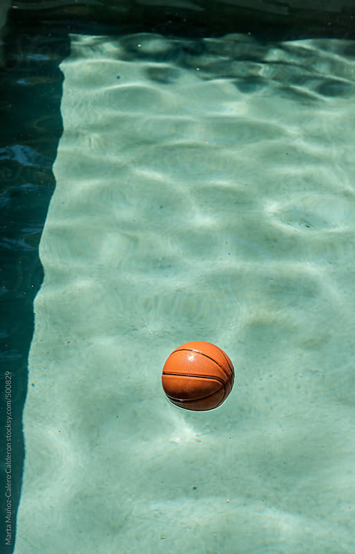 Basketball floating in a pool by Marta Muñoz-Calero Calderon for Stocksy United