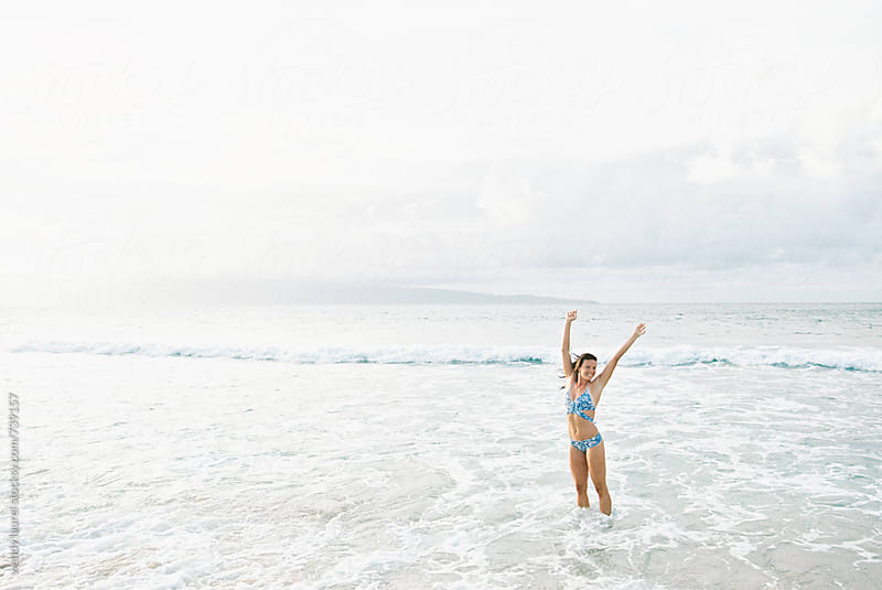 girl super happy on beach in ocean in hawaii on film by wendy laurel for Stocksy United