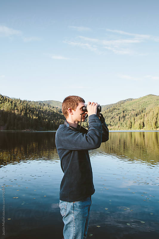 Man watching wildlife with binoculars at a lake by Justin Mullet for Stocksy United