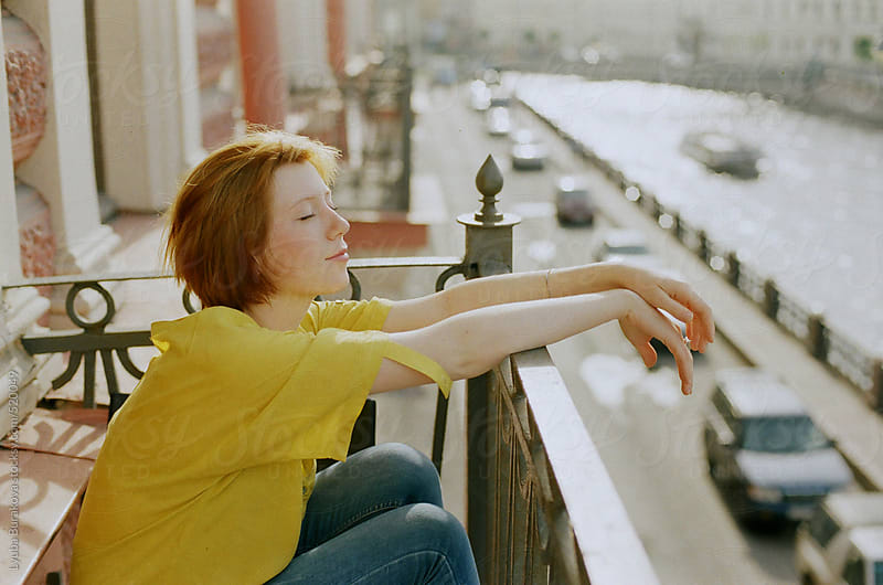 Portrait o young woman sitting on a balcony by Lyuba Burakova for Stocksy United