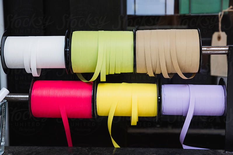 Small stand with colourful ribbon spools hanging by Lior + Lone for Stocksy United