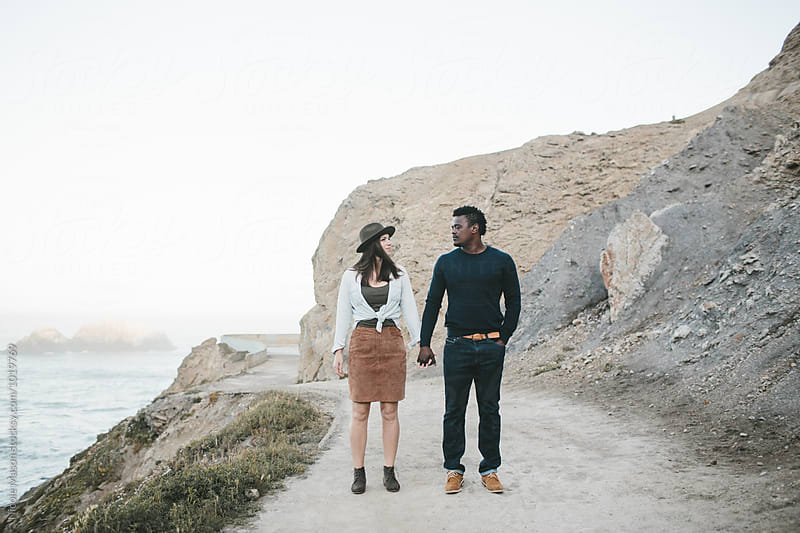 couple holds hands and looks at each other on path  by Nicole Mason for Stocksy United