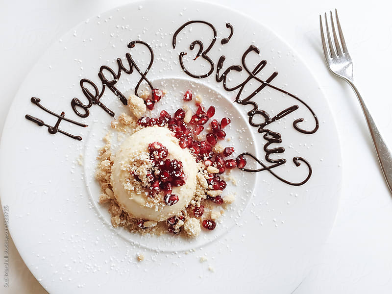 Dessert on a plate with happy birthday written in icing by Suzi Marshall for Stocksy United