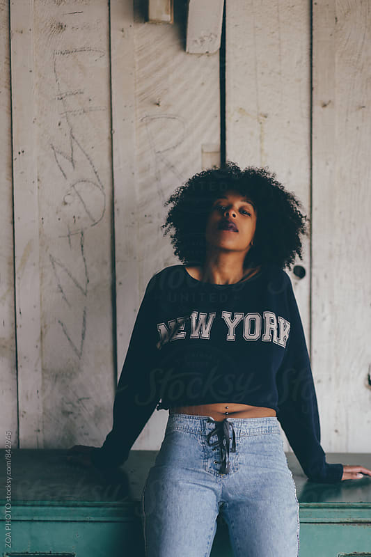 Curly haired woman in sweat shirt crop top by ZOA PHOTO for Stocksy United