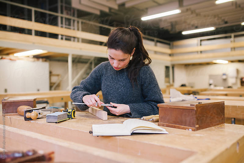 Female woodworker working on a bench, measuring a piece of wood by Ivo de Bruijn for Stocksy United