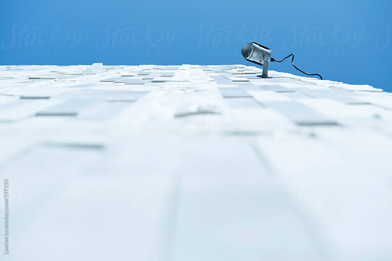 Monitor on a white wall under blue sky by Lawren Lu for Stocksy United