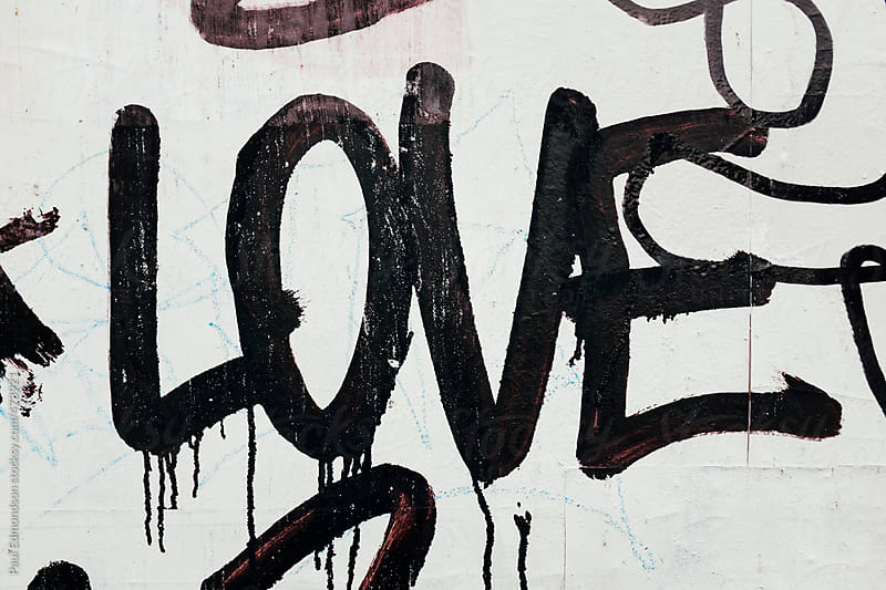 The word LOVE painted on exterior of building wall, close up by Paul Edmondson for Stocksy United