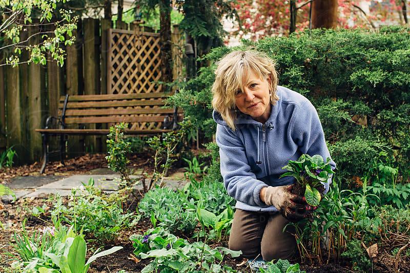 Smiling middle age woman gardening by Gabriel (Gabi) Bucataru for Stocksy United