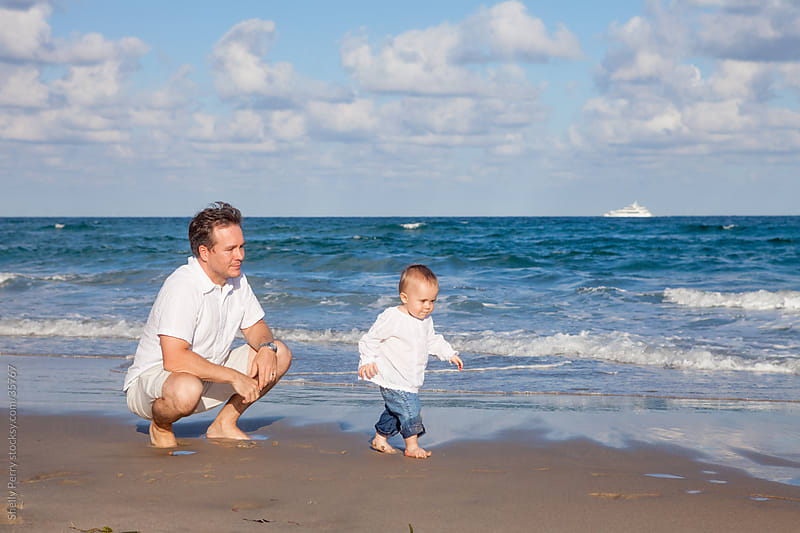 Dad Watching Toddler at the Beach by Shelly Perry for Stocksy United
