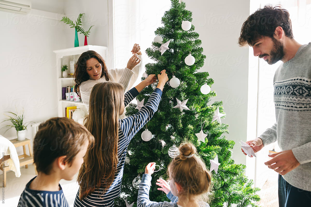 At Home Christmas Trees.Family Decorating Christmas Tree At Home By Bonninstudio