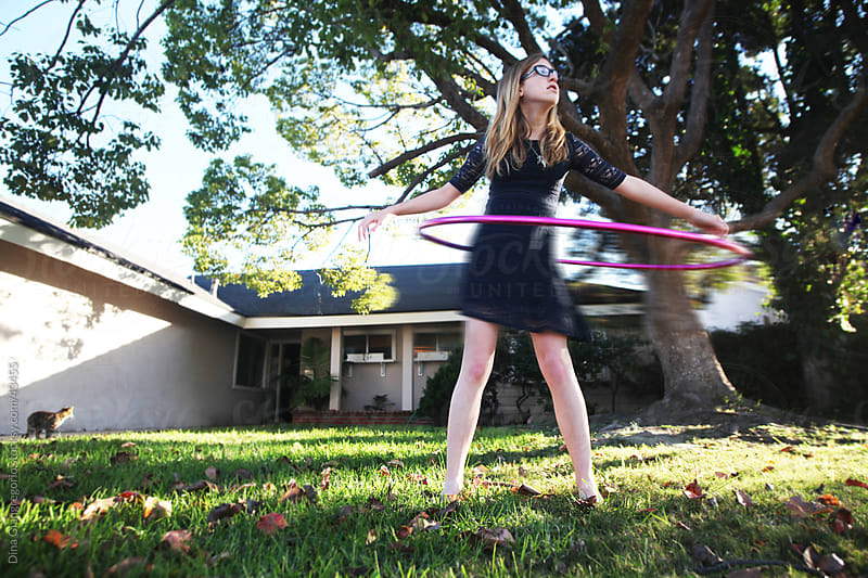 Pre-Teen girl with hula hoop in motion standing in front yard of a house by Dina Giangregorio for Stocksy United