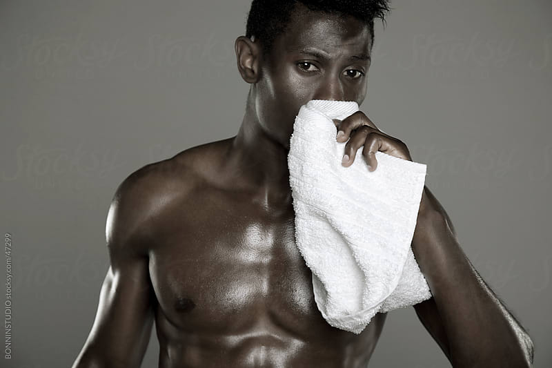 Portrait of an african athlete wiping sweat by BONNINSTUDIO for Stocksy United