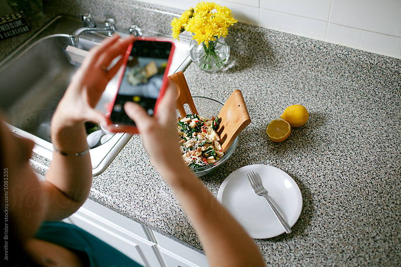 Woman taking photos of prepared salad on her cell phone  by Jennifer Brister for Stocksy United