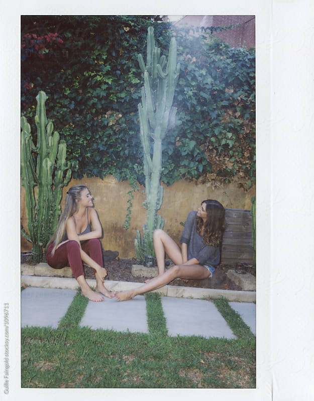 Smiling girlfriends sitting on ground and smiling at each other by Guille Faingold for Stocksy United