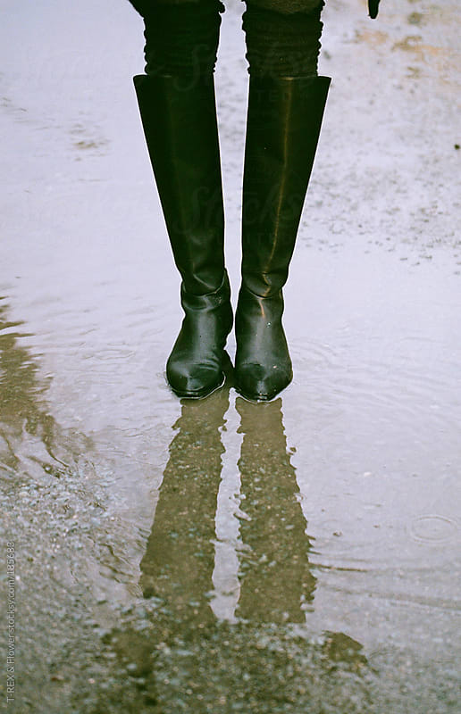 Woman standing in a puddle by T-REX & Flower for Stocksy United