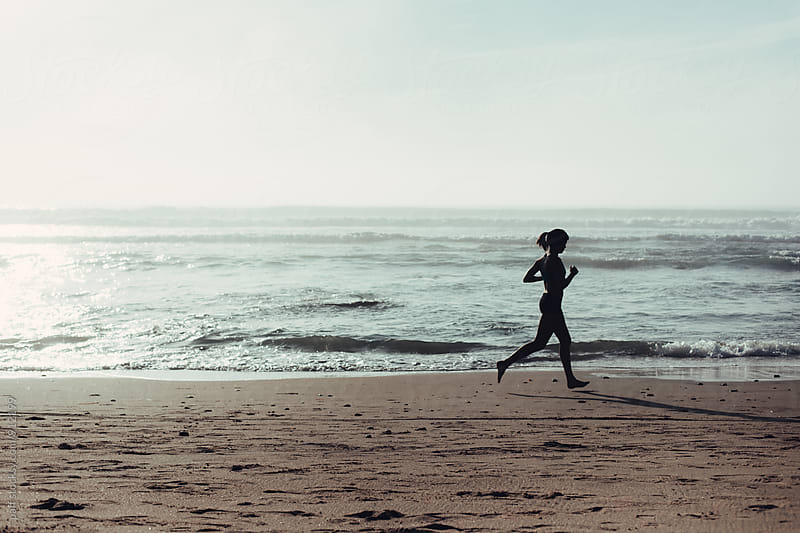Female athlete running along the seashore by paff for Stocksy United