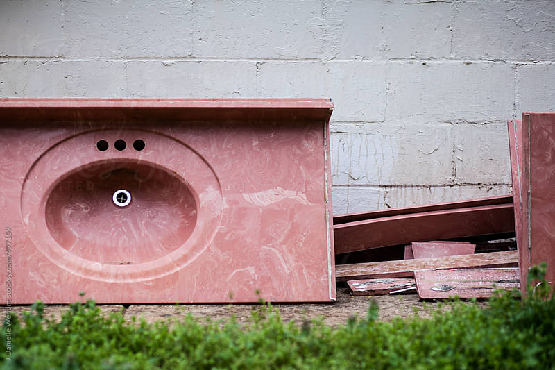 Pink sink and counter abandoned against building by J Danielle Wehunt for Stocksy United