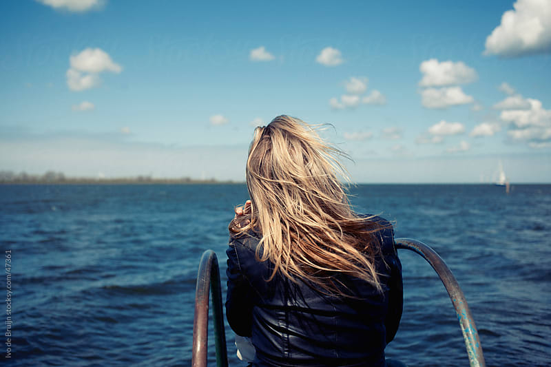 Blonde adolescent girl sitting at a pier overlooking a lake by Ivo de Bruijn for Stocksy United