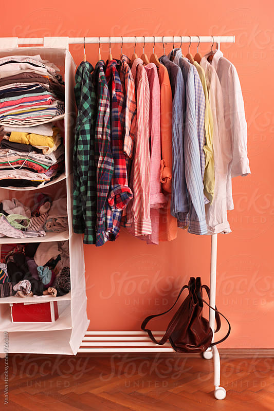 Colorful shirts and other clothes on hangers in girly room by Marija Mandic for Stocksy United