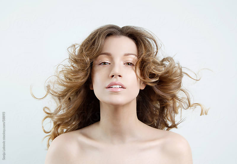 woman with long curly brown hair by Sonja Lekovic for Stocksy United