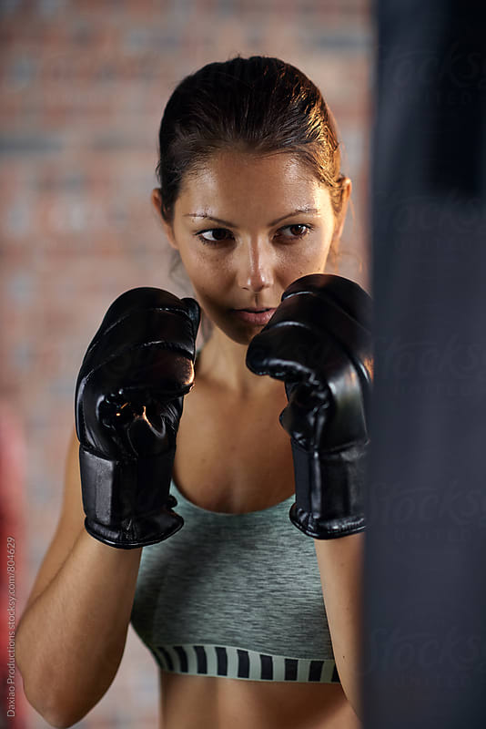 young fitness woman boxing on a punching bag  by Daxiao Productions for Stocksy United
