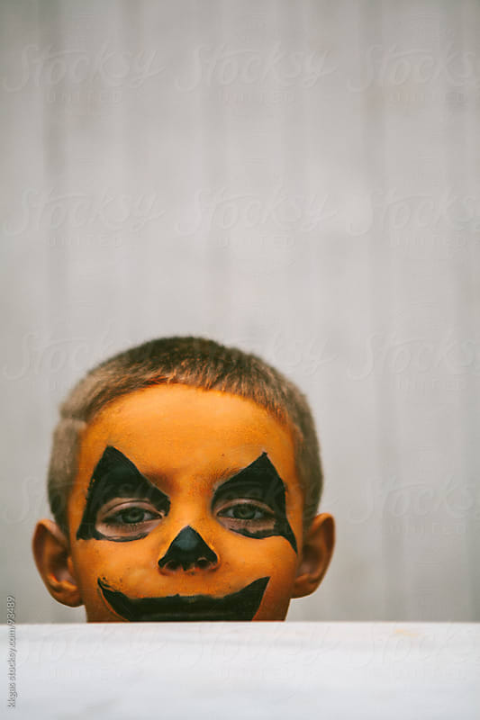 Little boy with jack-o-lantern face paint for Halloween by kkgas for Stocksy United