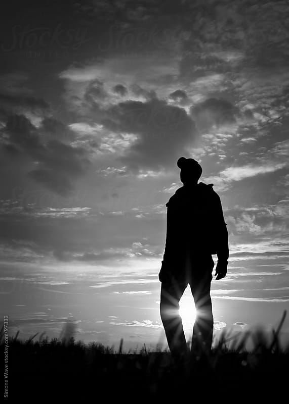 Silhouette of Man Standing in a Field against sunlight by GIC for Stocksy United