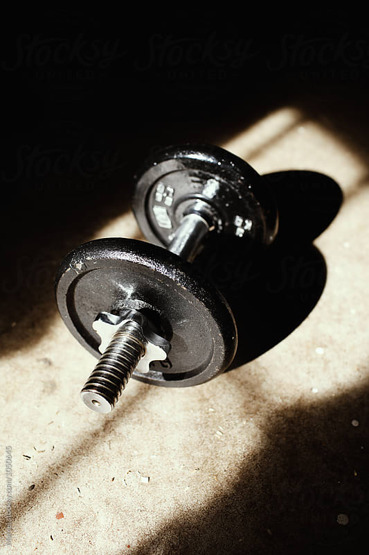 Iron dumbbells on the floor of a home gym by Marcel for Stocksy United