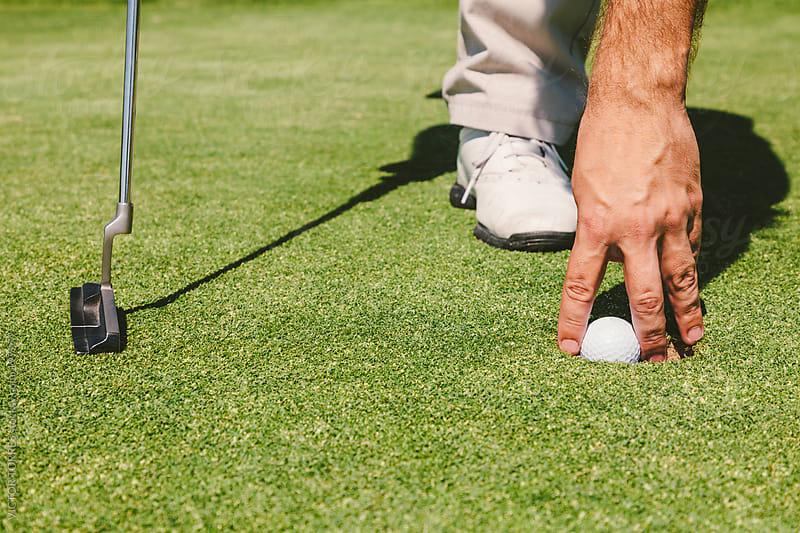 Golfer Picking the Ball from Inside the Hole by VICTOR TORRES for Stocksy United