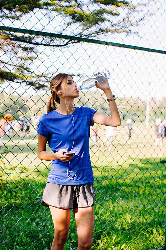 Young Girl Drinking Water After Running in the Park by Mosuno for Stocksy United
