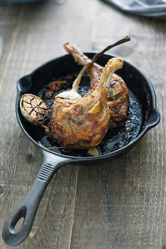 Roasted duck legs in a cast iron pan. by Darren Muir for Stocksy United