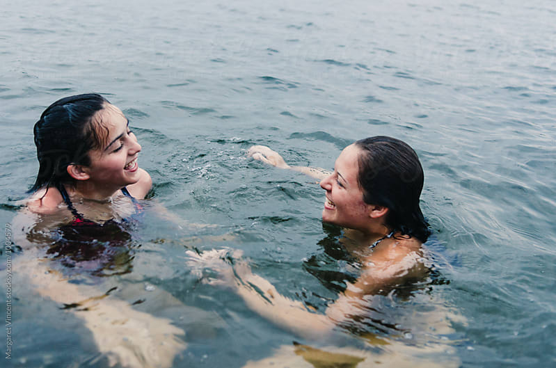 two teenage girls having fun in a lake by Margaret Vincent for Stocksy United
