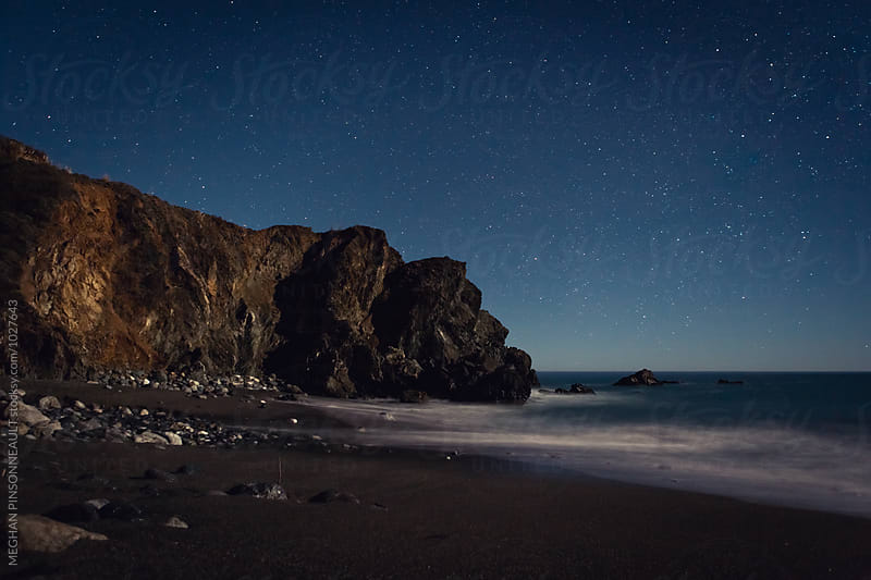 Moonlit Cliff on Beach with Stars and Waves by MEGHAN PINSONNEAULT for Stocksy United